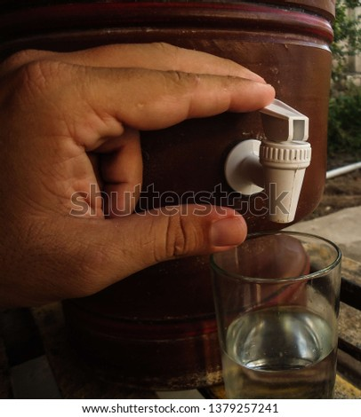 Hand of a young caucasian man pressing the clay filter tap. The clay filter is a genuinely Brazilian creation and provides excellent water quality. in April 2019. #1379257241