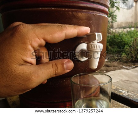 Hand of a young caucasian man pressing the clay filter tap. The clay filter is a genuinely Brazilian creation and provides excellent water quality. in April 2019. #1379257244