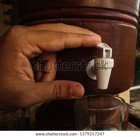 Hand of a young caucasian man pressing the clay filter tap. The clay filter is a genuinely Brazilian creation and provides excellent water quality. in April 2019. #1379257247