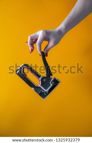 hand of a young woman holding a metal stapler, close-up on a yellow background, vertical shot