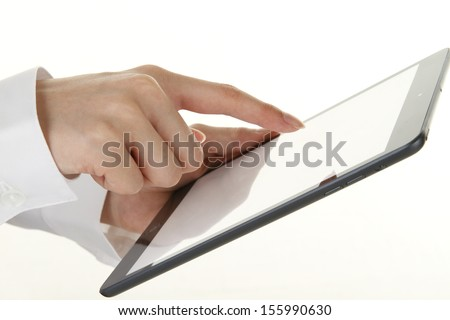 Hand of a young woman using a tablet personal computer