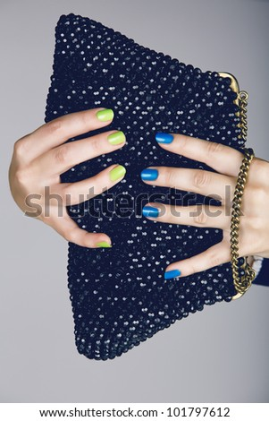 hand of a young woman with bright fashion manicure with green and blue nails holding a vintage beaded bag