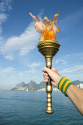 Hand of an athlete wearing Brazil colors sweatband holding sport torch against Rio de Janeiro Brazil skyline with Two Brothers Mountain