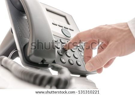 Hand of an operator dialing a phone number. Isolated over white background.