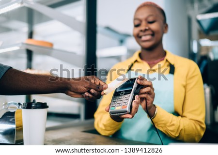 Hand of anonymous black man holding contactless credit card near payment terminal while buying takeaway food in modern cafe