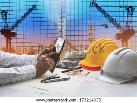 hand of architect working on table with tablet computer and working tool equipment against reflection of office building and crane construction for civil engineering and construction industry business