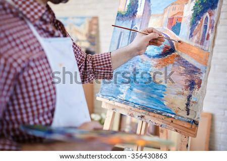 Shutterstock Hand of artist painting Italian landscape
