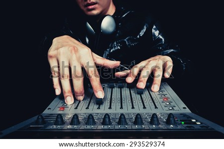 hand of asian handsome DJ, producer working on digital studio mixer for night club, radio , TV broadcasting background