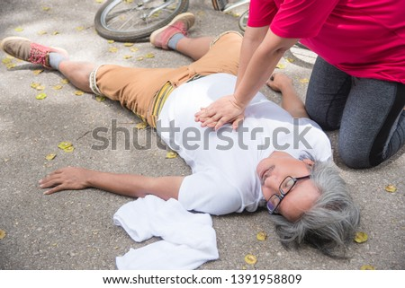 Hand of Asian Woman First Aid Emergency CPR on Heart Attack Senior senior man with cardiac arrest while exercise in park. Basic life support concept . #1391958809