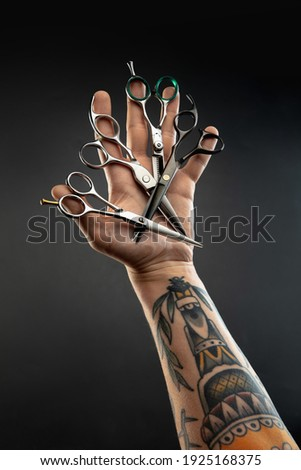 Hand of barber with equipment set on black table background. Close up different sccissors, razors, professional tools of hairdresser. Professional occupation, art, self-care concept. Magazine. Photo stock ©