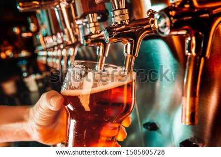 Hand of bartender pouring a large lager beer in tap. Bright and modern neon light, males hands. Pouring beer for client. Side view of young bartender pouring beer while standing at the bar counter. Photo stock ©