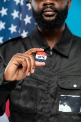 Hand of bearded African-american male security in black uniform showing you vote insignia while standing against stars-and-stripes flag
