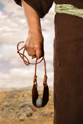 Hand of biblical David holding sling shot with stone
