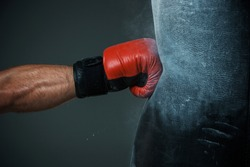 Hand  of boxer and punching bag over black background