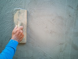 Hand of builder worker man holds a trowel for worker plastering at cement wall or skimming coating on plaster walls, Closeup hand construction plastering wet cement