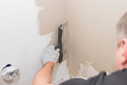 hand of builder worker plastering at wall.Renovation workers hand plastering the wall.Construction finishing works.work aligns with a spatula wall.process of applying layer of putty trowel