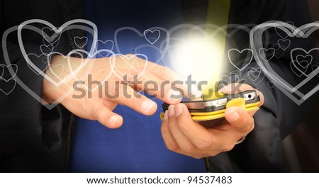 Hand of business man send heart on mobile phone as Valentine concept