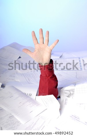 hand of business man sticking out of a desk full of papers