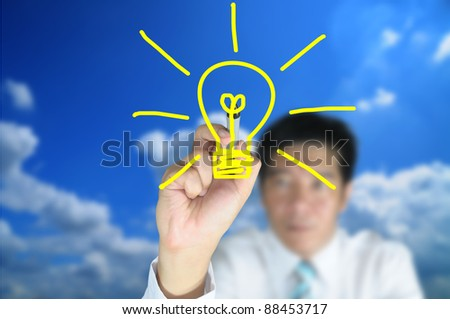 Hand of business man write light bulb on touch screen tablet