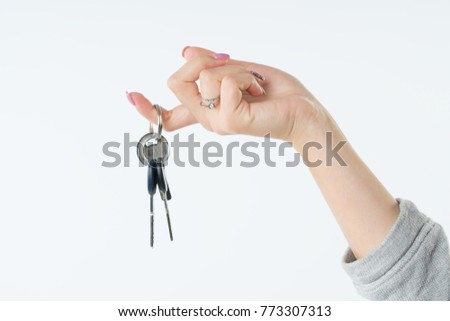 Hand of business woman or real estate agent with keys from new flat or house hanging on the finger. She welcomes to buy a flat or house. Isolated on white background