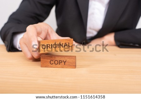 Hand of businessman choosing wood blog with icon and word Original and Copy. #1151614358