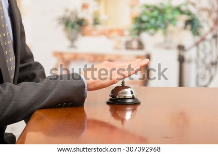 hand of businessman customer ringing hotel bell in reception desk close up selective focus