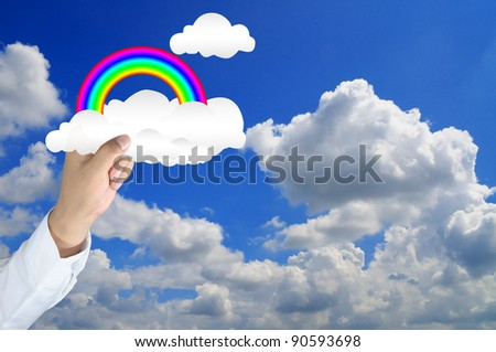 hand of businessman hold rainbow and cloud to the blue sky