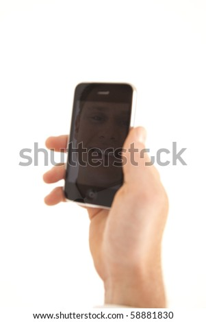 Hand of businessman holding cell phone with refection of face