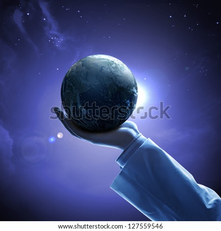 Hand of businessman holding earth planet against illustration background