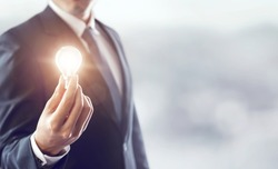 Hand of businessman holding illuminated light bulb, idea, innovation and inspiration concept, background for copy.