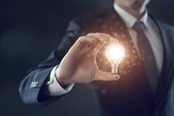 Hand of businessman holding illuminated light bulb, idea, innovation and inspiration concept.