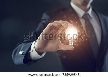 Hand of businessman holding illuminated light bulb, idea, innovation and inspiration concept. #735929545