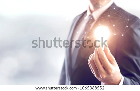 Hand of businessman holding illuminated light bulb, idea, innovation and inspiration concept, copy space. #1065368552