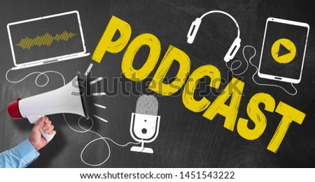 hand of businessman holding megaphone or bullhorn against blackboard with podcasting symbols and text PODCAST