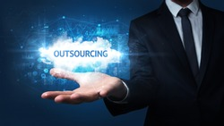 Hand of Businessman holding OUTSOURCING inscription, successful business concept