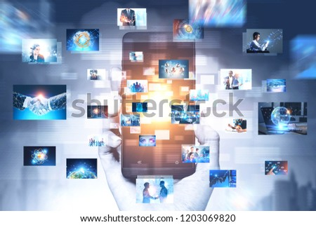 Hand of businessman holding smartphone in gray city with many business themed pictures emerging from it. Concept of hi tech and big data. Toned image double exposure