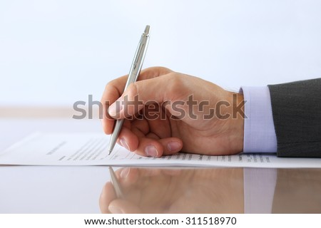 Hand of businessman in suit filling and signing with silver pen employment contract form lying on table with reflection closeup. Business success, agreement, paperwork or lawyer concept