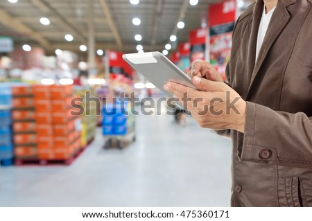 Hand of Businessman, Manger use Mobile Tablet in supermarket with Blur Background of product display on shelves in Supermarket or Hypermarket warehouse