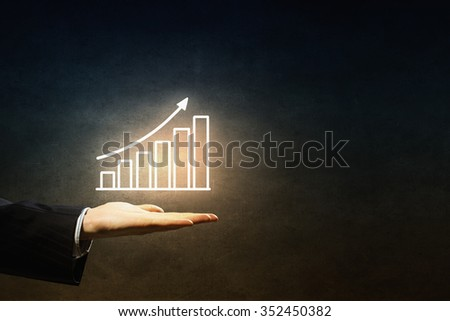Hand of businessman on dark background showing glowing business growth concept