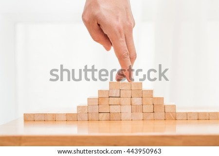 Hand of businessman pointing on top of wood block #443950963