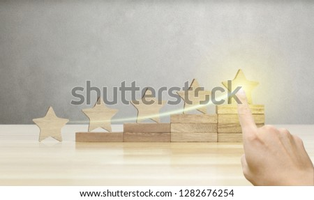 Hand of businessman pointing wooden five star shape on table, The best excellent business services rating customer experience concept. #1282676254