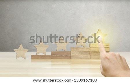 Hand of businessman pointing wooden five star shape on table, The best excellent business services rating customer experience concept. #1309167103