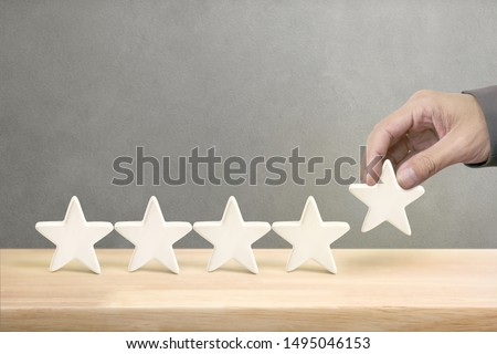 Hand of businessman putting increase white five star shape on table, The best excellent business services rating customer experience concept. #1495046153