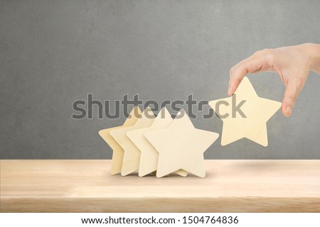 Hand of businessman putting increase wood five star shape on table, The best excellent business services rating customer experience concept.