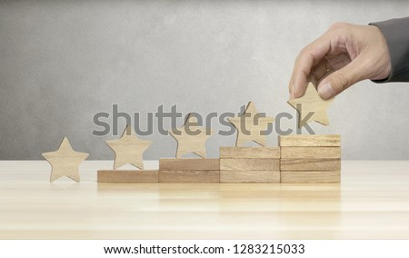 Hand of businessman putting wooden five star shape on table, The best excellent business services rating customer experience concept. #1283215033