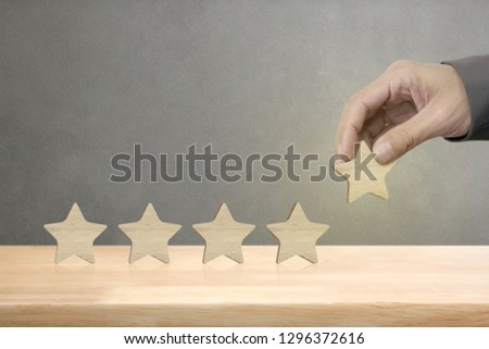 Hand of businessman putting wooden five star shape on table, The best excellent business services rating customer experience concept. #1296372616