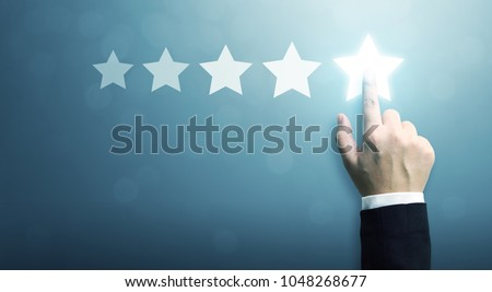 Hand of businessman touching five star symbol to increase rating of company concept, Copy space background for your title #1048268677