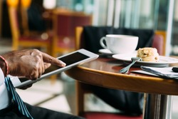 Hand of businessman using digital tablet while having breakfast in the cafe