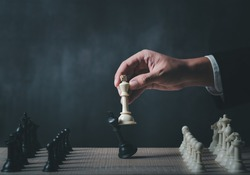 hand of businessman wearing suit moving chess figure in competition success play. strategy,teamwork, management or leadership concept.