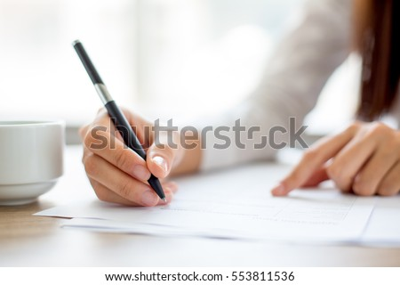 hand of businesswoman writing...